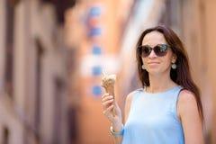 在获得乐趣和吃冰淇凌的街道上的可爱的妇女 Y 库存图片