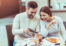 在获得乐趣和吃薄饼的爱的夫妇在咖啡馆 免版税库存图片