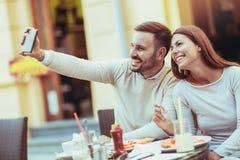 在获得乐趣和吃薄饼的爱的浪漫夫妇在咖啡馆 库存图片