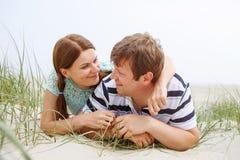 在获得的爱的年轻愉快的夫妇在海滩的沙丘的乐趣 免版税库存图片