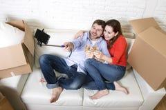在获得的长沙发的愉快的夫妇一起庆祝香槟的乐趣 库存图片
