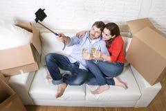 在获得的长沙发的愉快的夫妇一起庆祝香槟的乐趣 免版税库存图片