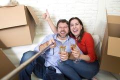 在获得的长沙发的愉快的夫妇一起庆祝香槟的乐趣 库存照片