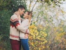 在获得被编织的毛线衣的年轻有吸引力的夫妇乐趣 库存图片