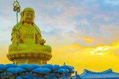 在菩萨雕象后的日出在Haedong Yonggungsa寺庙在韩国 免版税库存图片