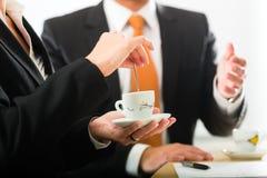 在营业所饮用的咖啡的Businesspersons 免版税图库摄影