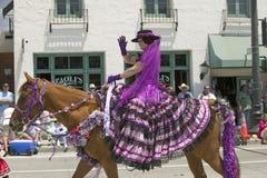 在营业日游行下降状态街道,圣塔巴巴拉,加州,老西班牙天Fies期间,有紫色西班牙语的妇女穿戴骑乘马 免版税库存照片