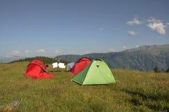 在营地的三个帐篷与垂悬由干燥决定的洗衣店在线 免版税库存图片