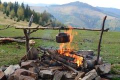 在营火的水壶 免版税库存照片