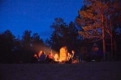 在营火附近的游人在晚上 库存图片