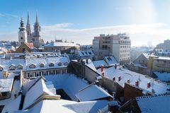 在萨格勒布的看法在与雪的冬天期间有对教会和大教堂和多雪的屋顶,萨格勒布,克罗地亚塔的看法  图库摄影