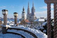 在萨格勒布的看法在与雪的冬天期间有对教会和大教堂和就座区域塔的看法与laterns 库存照片