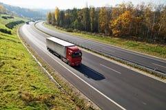 在落叶林之间的高速公路有在秋天颜色的叶子的,高速公路乘驾三卡车 免版税库存图片
