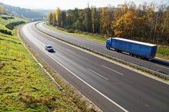 在落叶林之间的高速公路有在秋天颜色的叶子的,高速公路是蓝色卡车和客车 库存照片