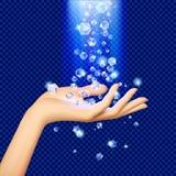 在落在妇女` s手上的蓝色光下的金刚石 免版税库存图片