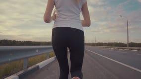 在落日的竞技课 一个运动的女孩一件白色T恤杉的和有长的头发的沿一条空的轨道跑 股票视频