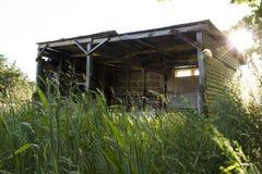 在落日的老被放弃的棚子 免版税图库摄影