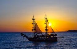 在落日的背景的两桅的帆船 免版税库存图片