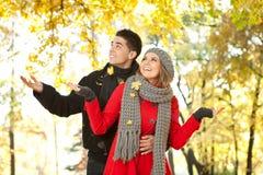 在落的叶子的夫妇,爱在秋天公园 免版税图库摄影