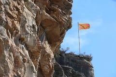 在落矶山脉Sant Miquel del Fai的加泰罗尼亚的旗子在Bigas卡塔龙尼亚巴塞罗那西班牙 免版税库存图片