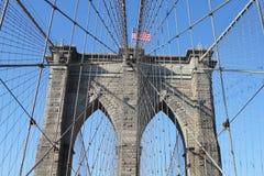 在著名布鲁克林大桥顶部的美国国旗 免版税库存照片