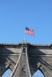 在著名布鲁克林大桥顶部的美国国旗 免版税图库摄影