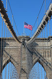 在著名布鲁克林大桥顶部的美国国旗 图库摄影