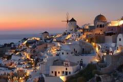 在著名风车的日落在美丽的Oia村庄,圣托里尼 免版税库存图片