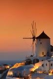 在著名风车的日落在美丽的Oia村庄,圣托里尼 图库摄影