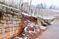 在葡萄园水和雪损伤的破碎石块墙壁 库存图片