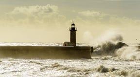 在葡萄牙语大西洋的巨大的波浪打击的灯塔 库存照片
