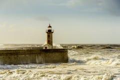 在葡萄牙语大西洋的巨大的波浪打击的灯塔 库存图片