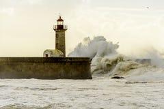 在葡萄牙语大西洋的巨大的波浪打击的灯塔 免版税库存照片