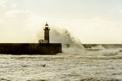在葡萄牙语大西洋的巨大的波浪打击的灯塔 免版税库存图片
