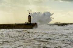 在葡萄牙语大西洋的巨大的波浪打击的灯塔 图库摄影