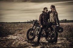 在葡萄酒习惯摩托车的年轻,时髦的咖啡馆竟赛者夫妇在领域 免版税库存图片