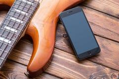 在葡萄酒低音吉他的智能手机大模型 免版税库存图片