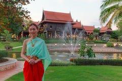 在葡萄酒减速火箭的传统泰国服装的年轻美好的泰国亚洲妇女选矿在对受欢迎的客人文化的泰国的等待 库存照片