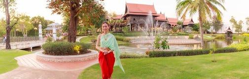 在葡萄酒减速火箭的传统泰国服装的年轻美好的泰国亚洲妇女选矿在对受欢迎的客人文化的泰国的等待 免版税库存图片