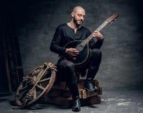 在葡萄酒凯尔特衣裳打扮的传统民间音乐家坐一个木箱并且弹曼陀林 免版税库存照片