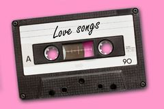 在葡萄酒卡型盒式录音机磁带写的爱情歌曲,桃红色背景 图库摄影