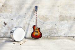 在葡萄酒墙壁前面的电吉他和鼓 库存图片