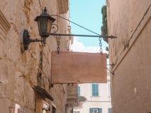 在葡萄酒家背景的木垂悬的长方形标志  老城市,淡色,天空蔚蓝 免版税图库摄影