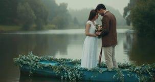 在葡萄酒布料的美好的爱恋的夫妇拿着势均力敌美妙的花的和的身分,当时 影视素材