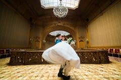 在葡萄酒房子的典雅的婚礼夫妇跳舞老冰屑玻璃天花板前面的  免版税库存图片
