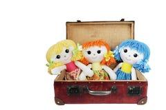 在葡萄酒手提箱的三个布洋娃娃 免版税图库摄影