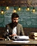 在葡萄酒打字机的有胡子的人类型 有胡子的人打字研究论文 在衣服工作的商人在书桌 库存图片