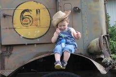 年轻在葡萄酒拖拉机的男孩吹的泡影 免版税库存图片