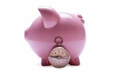 在葡萄酒指南针旁边的桃红色存钱罐 免版税库存图片