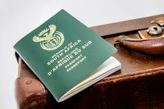 在葡萄酒旅行袋子旁边的一本南非护照 这个图象可以用于代表旅行或移民 免版税库存图片